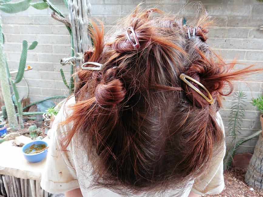 Photo of me with barrettes in my hair getting ready to henna my hair with Light Mountain Henna in red.
