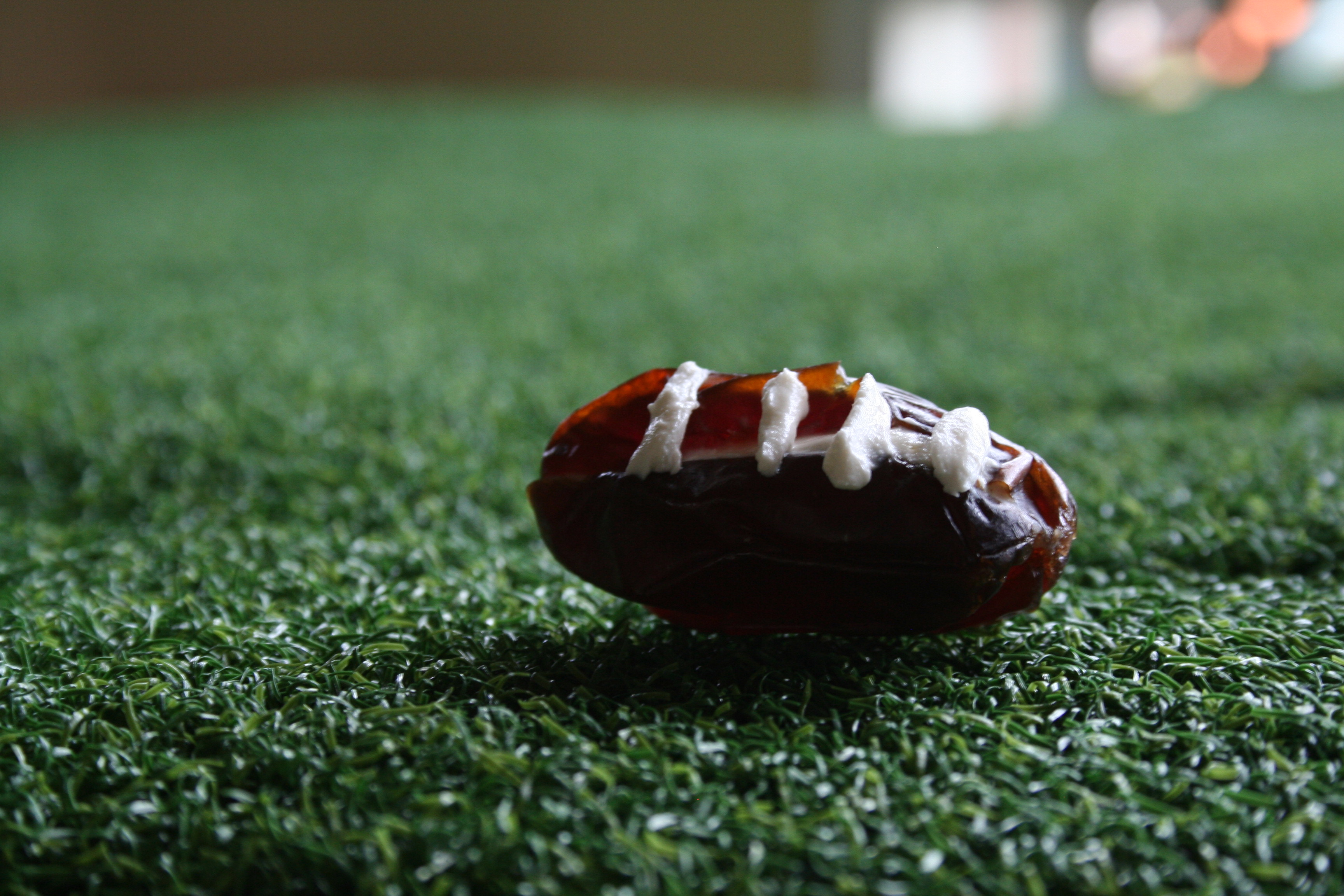 Stuffed Date Football close up on fake grass.