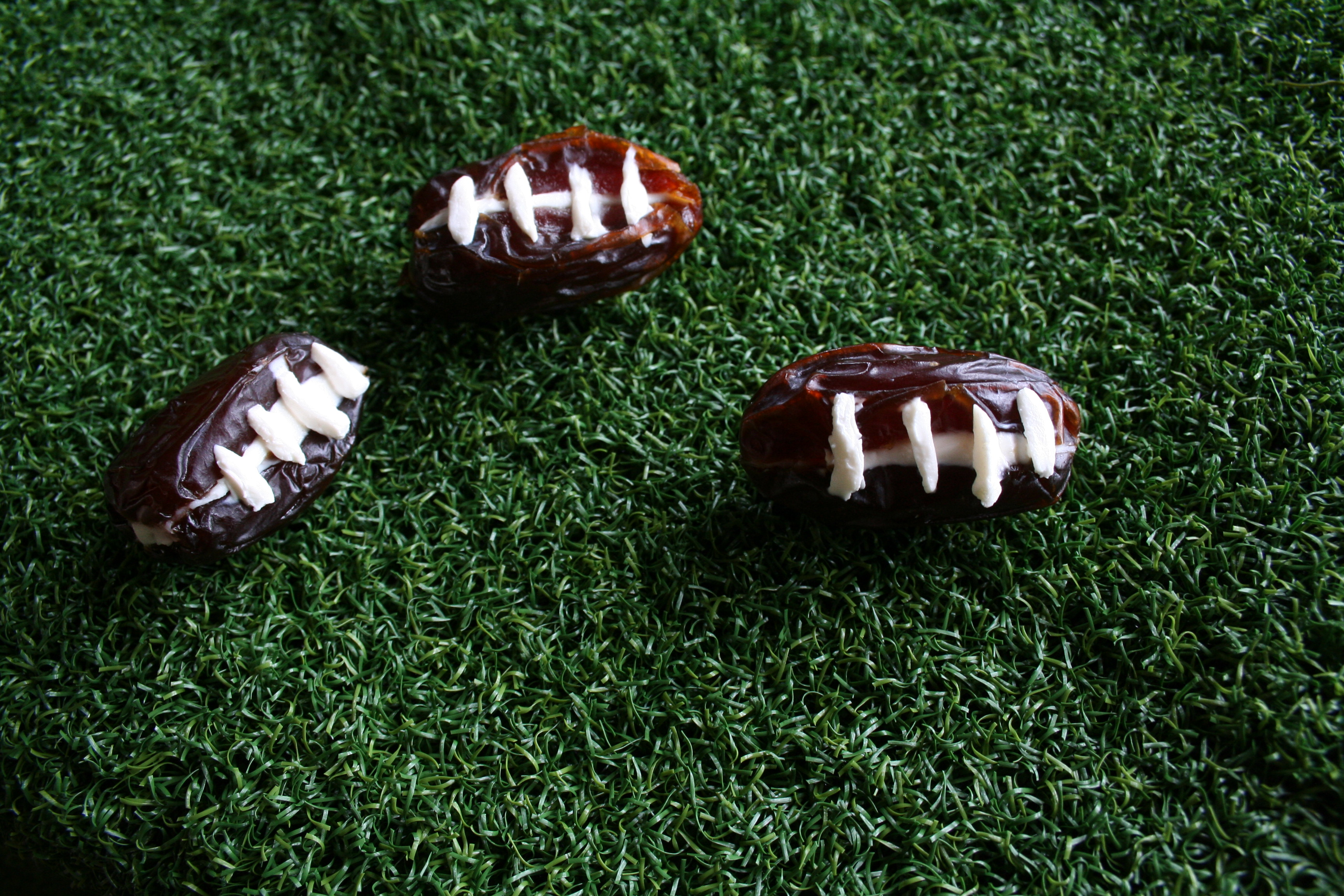 Stuffed Date Footballs on fake grass.