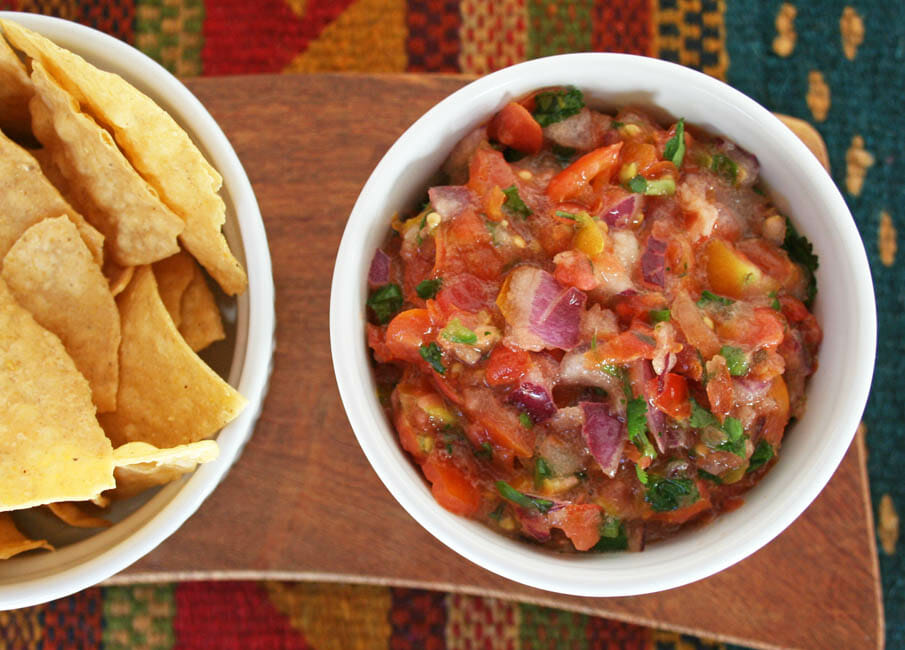 Salsa Serrano with chips on a cutting board.