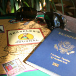 Photo of a passport, travel journal, and sunglasses.