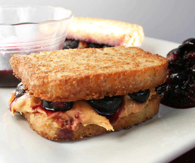 Peanut Butter and Blueberry French Toast close up with blueberry dipping sauce in background.
