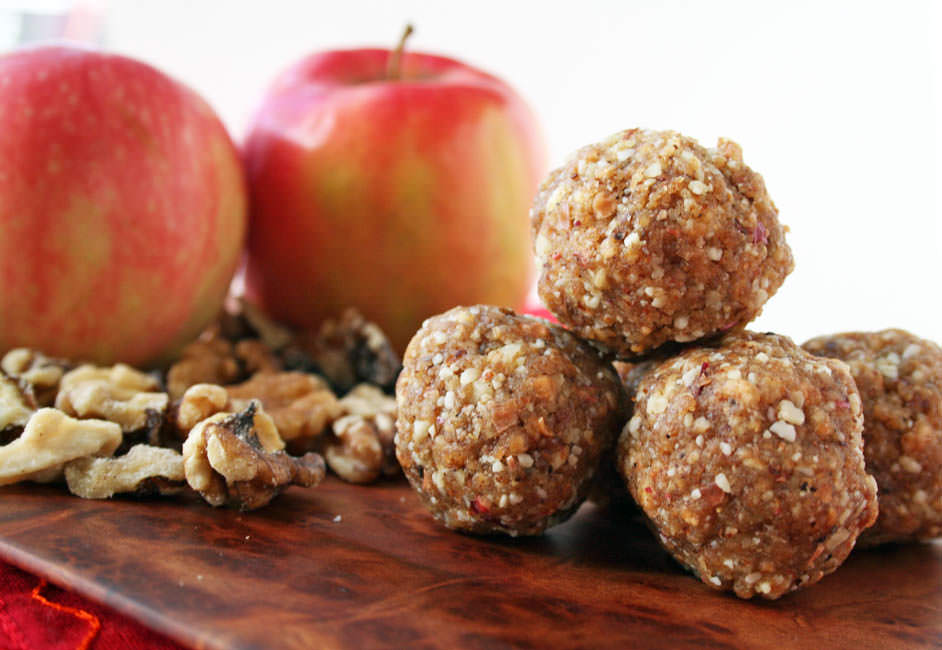 Apple Walnut Balls horizontal close up. Gala apples and walnuts in the background.