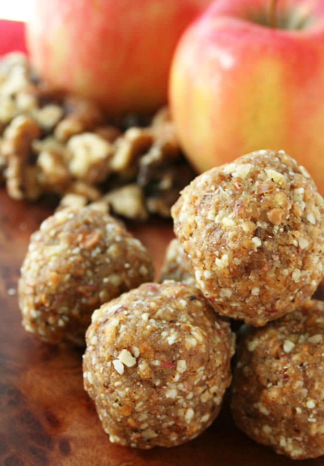 Apple Walnut Balls vertical close up. Gala apples and walnuts in the background.