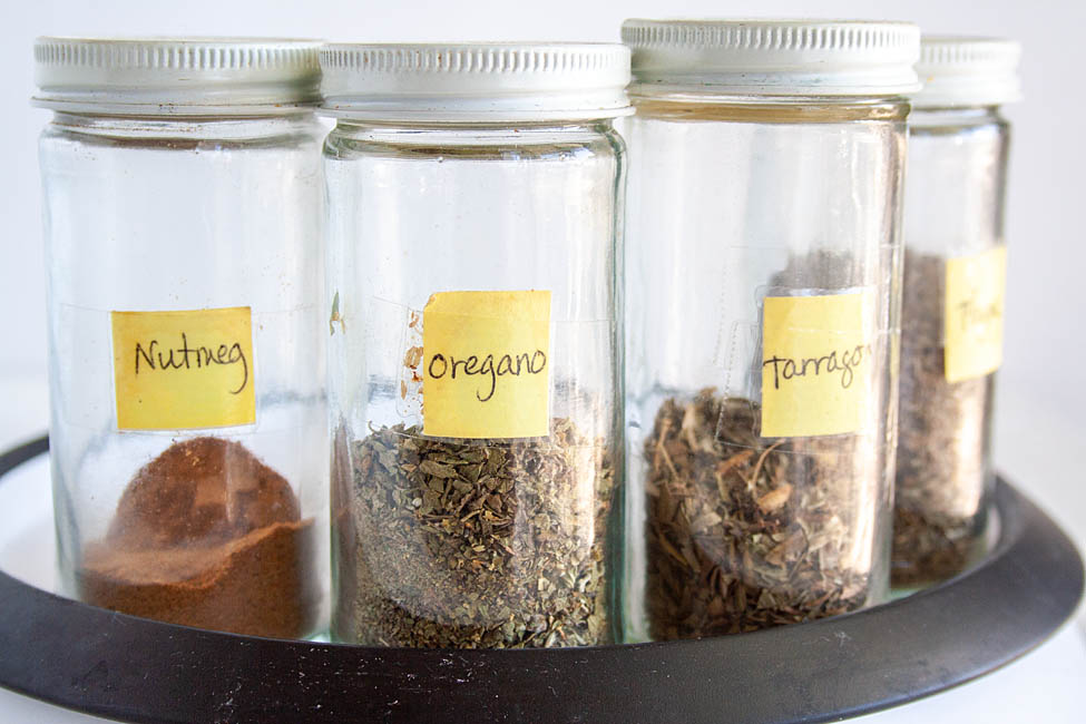 Jars of herbs including nutmeg, oregano, tarragon, and thyme.