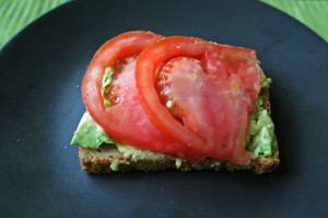 Avocado mashed with tomato slices on toast.