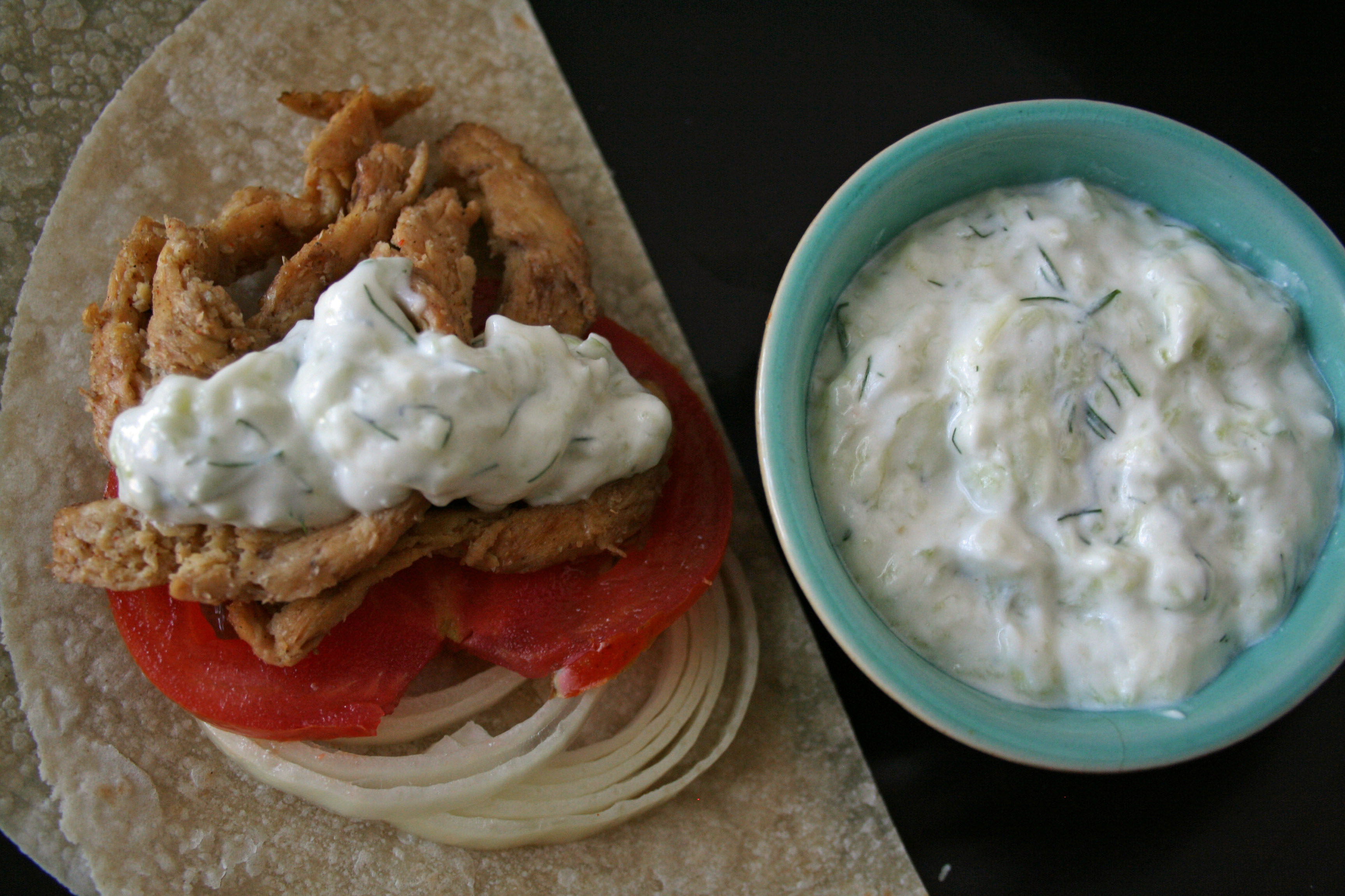 Vegan Gyros with Tzatziki open faced on a plate.