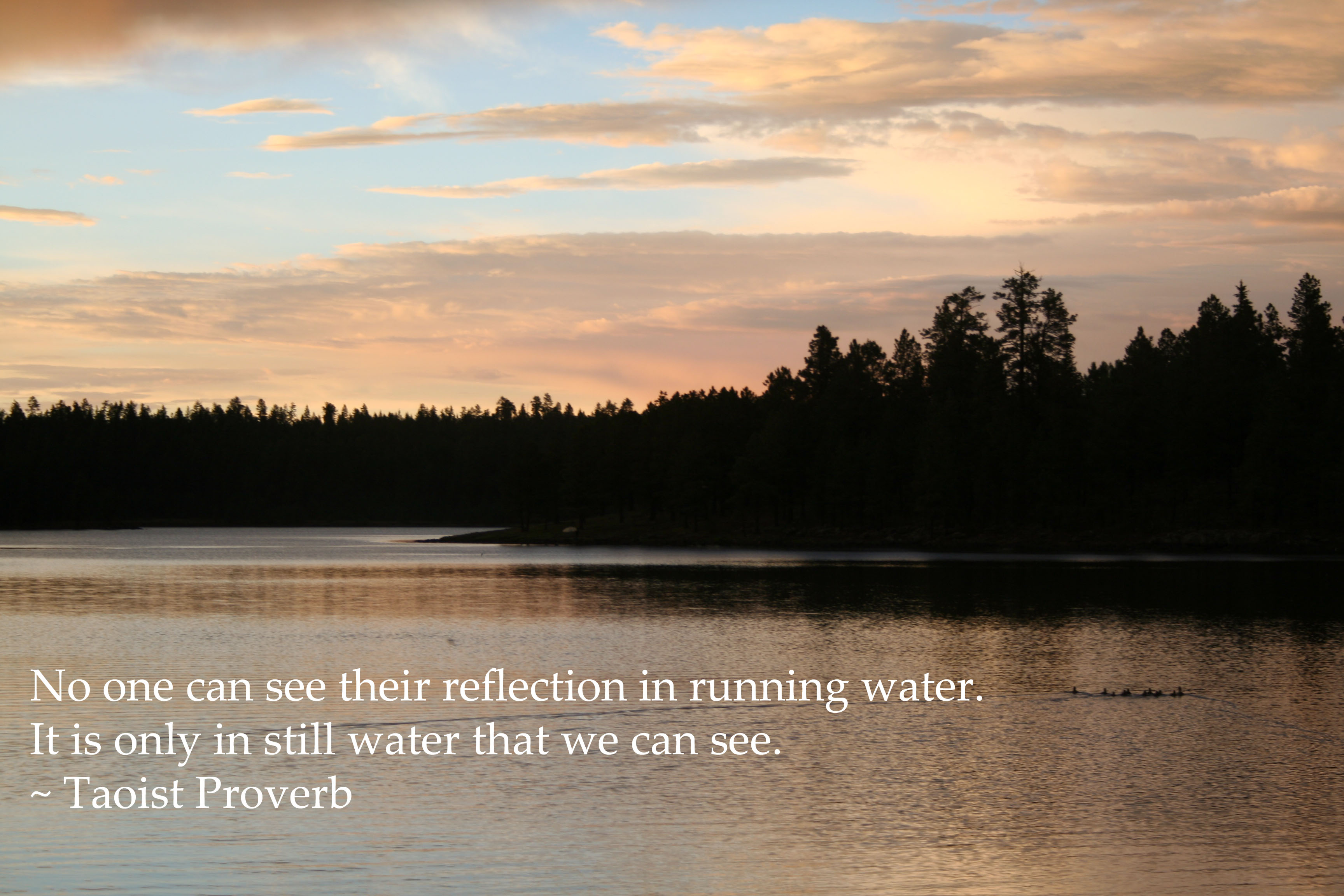 """""""No one can see their reflection in running water. It is only in still water that we can see."""" - Taoist proverb written on photo of lake at sunset."""