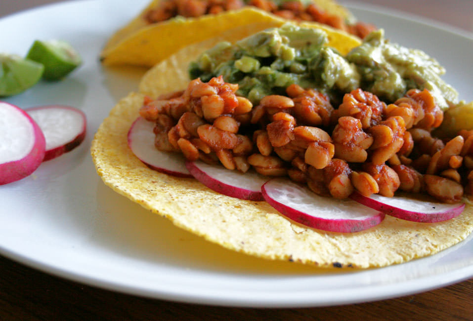 BBQ Tempeh Tacos with Grilled Pineapple Guacamole close up with key limes and radish slices.