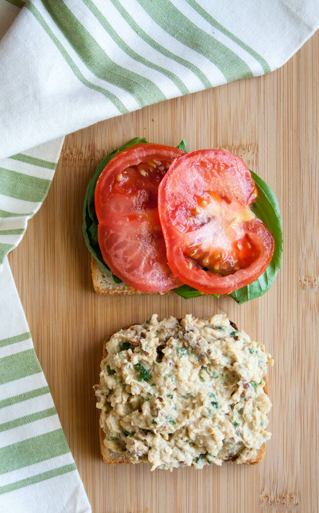 Sun-Dried Tomato and Basil Chickpea Salad Sandwich open faced on cutting board.