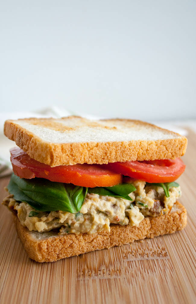 Sun-Dried Tomato and Basil Chickpea Salad Sandwich on cutting board.