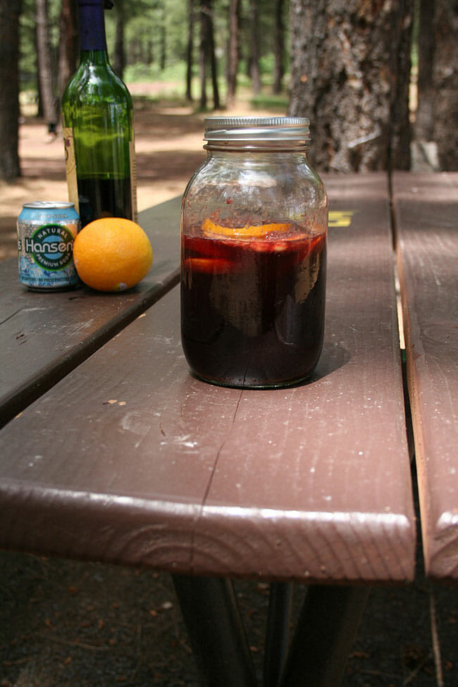 Camping Sangria on a picnic table with wine, club soda, and an orange in the background.