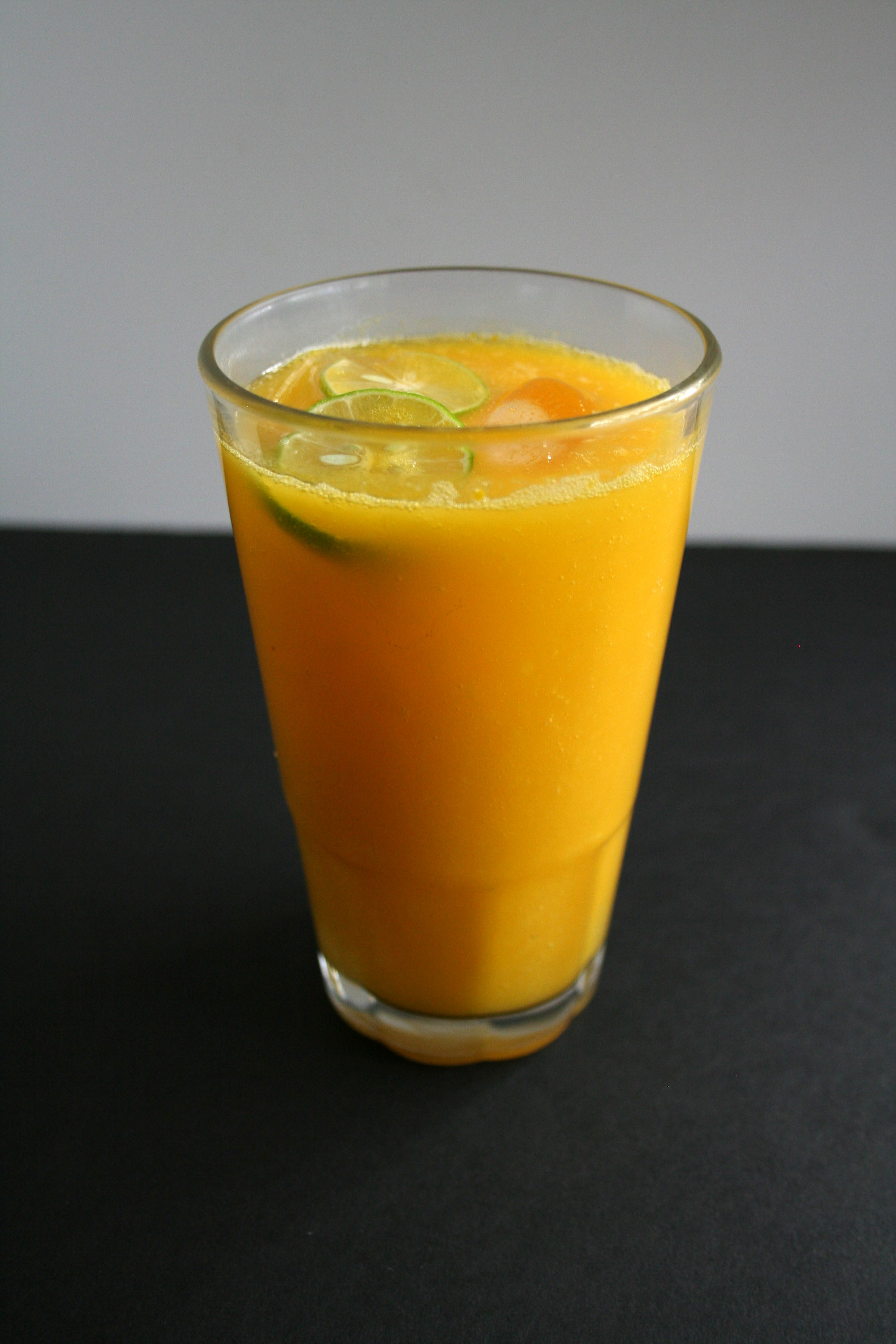 Mango Cocktail in a tall glass with a slice of lime.
