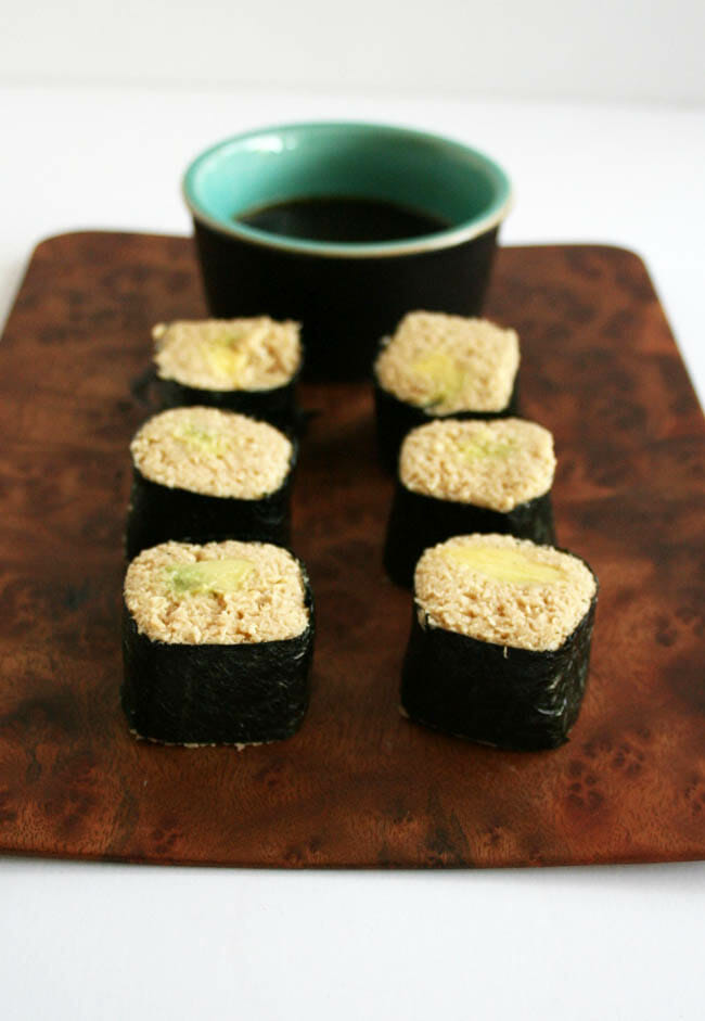 Avocado Sushi Rolls with Parsnip Rice on cutting board with dipping sauce.
