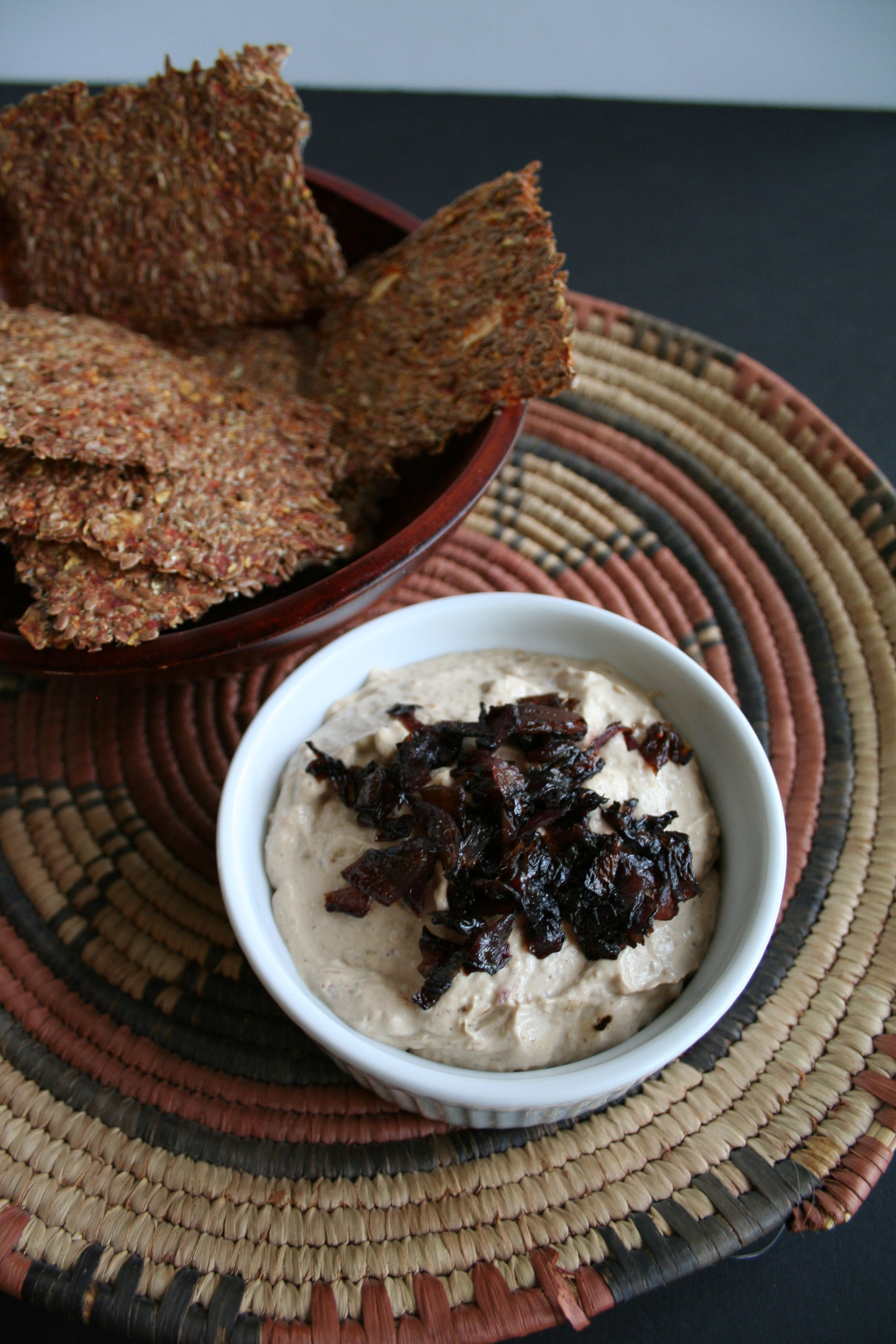Caramelized Red Onion Dip with flax crackers in the background.