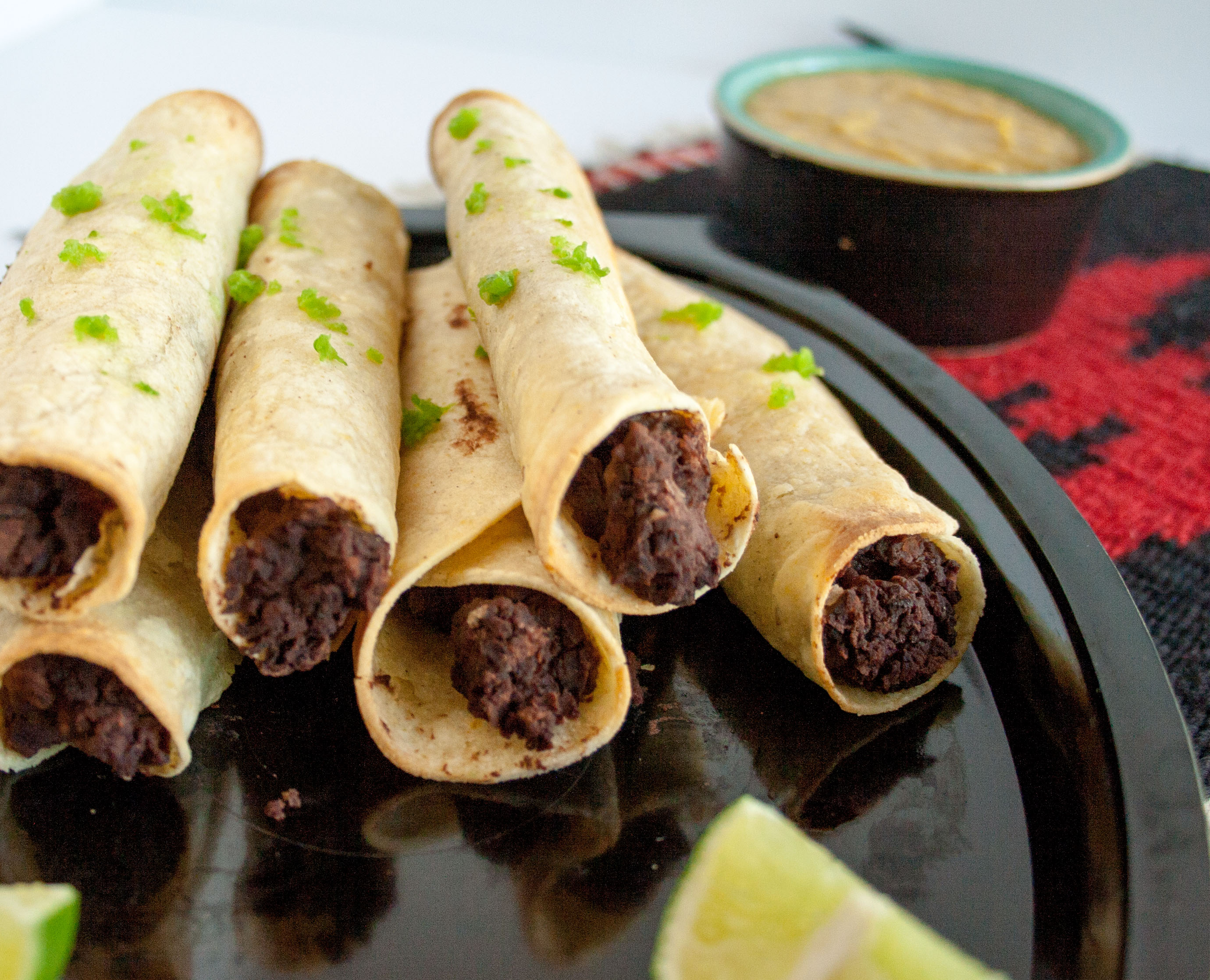 Bean Taquitos with Vegan Nacho Cheese close up.
