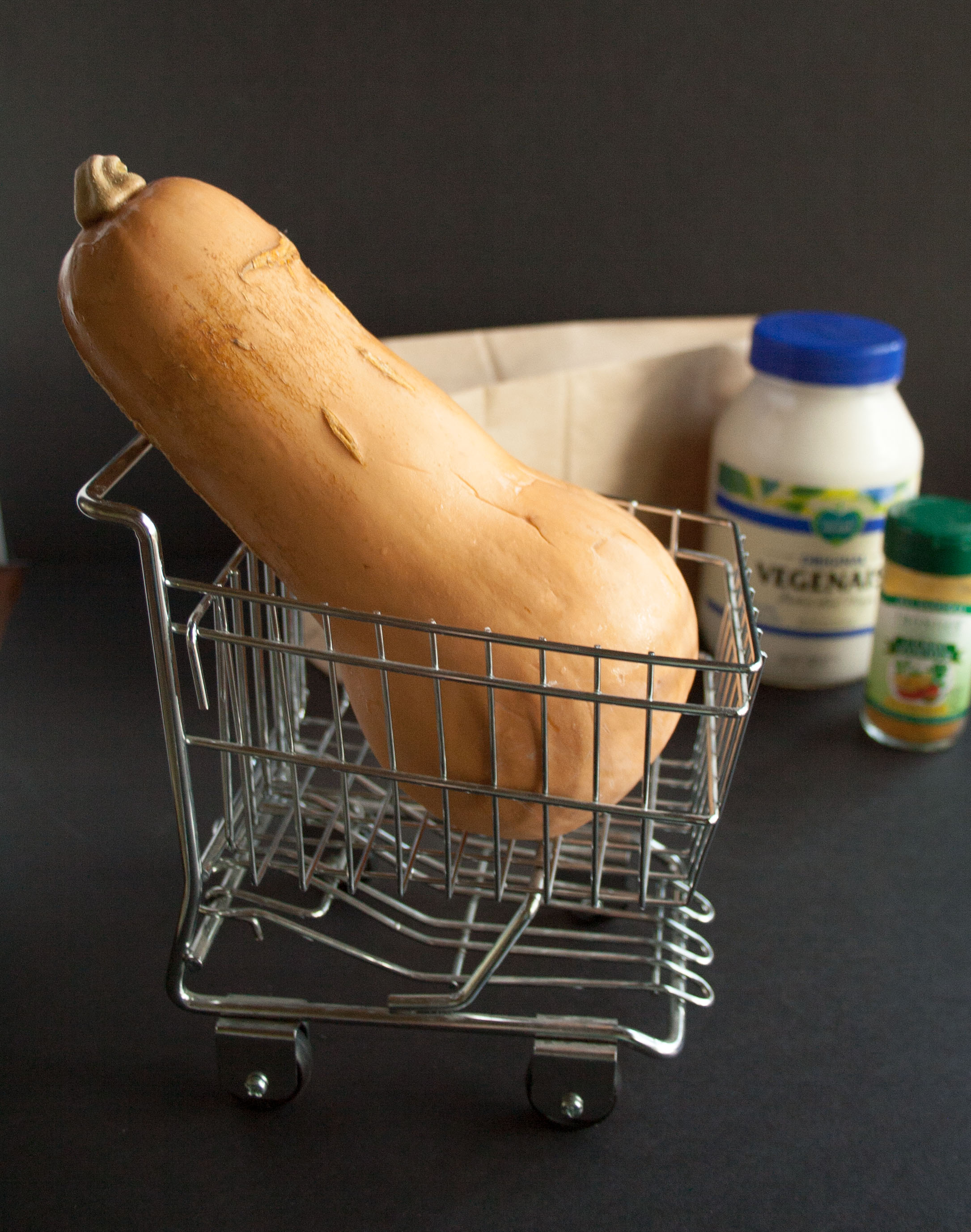 Butternut Squash Fries with Curry Mayo ingredients in background and squash in a mini shopping cart in foreground.