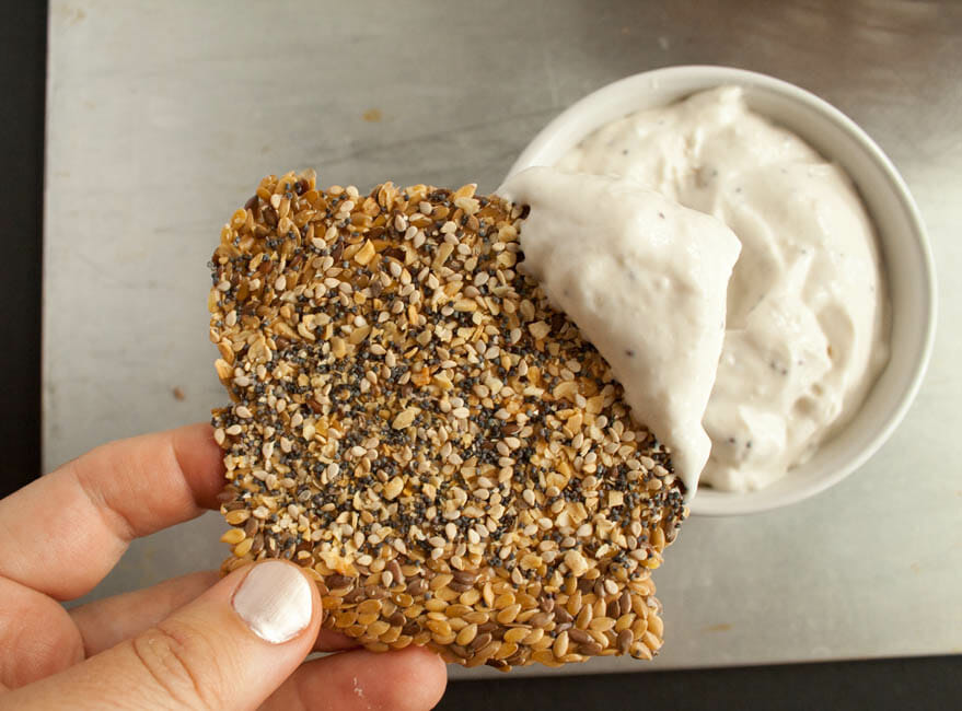 Everything Bagel Flax Crackers in hand with dip.