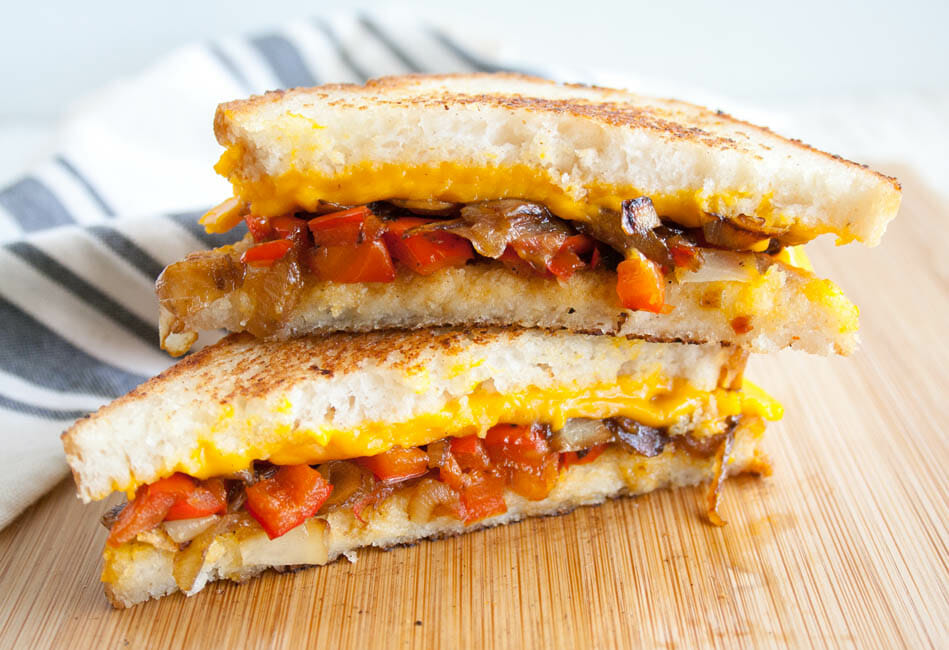 Vegan Grilled Cheese with Caramelized Onions and Red Pepper on cutting board.