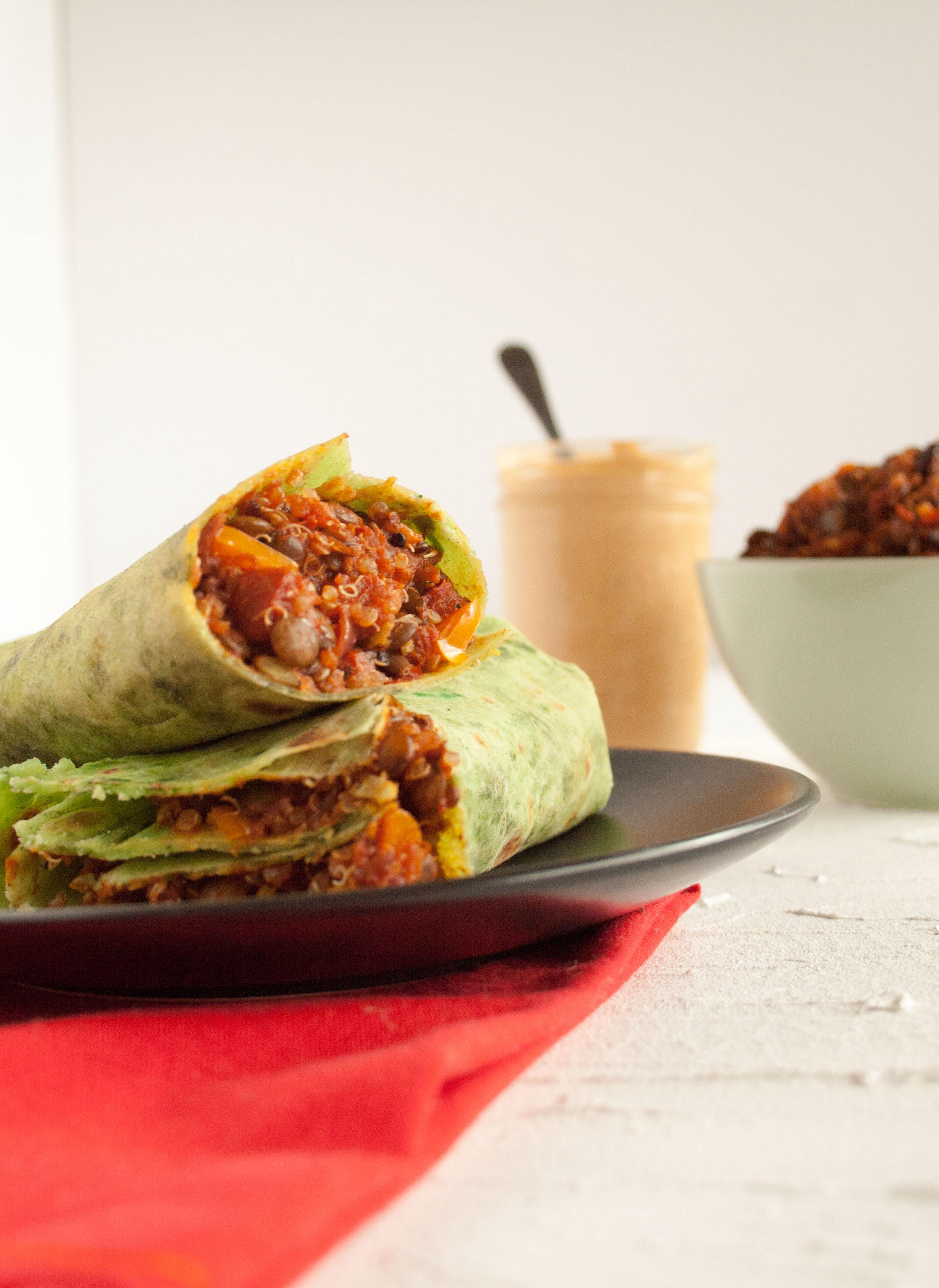 Lentil Quinoa Burritos with Chipotle Sauce with ingredients in the background.
