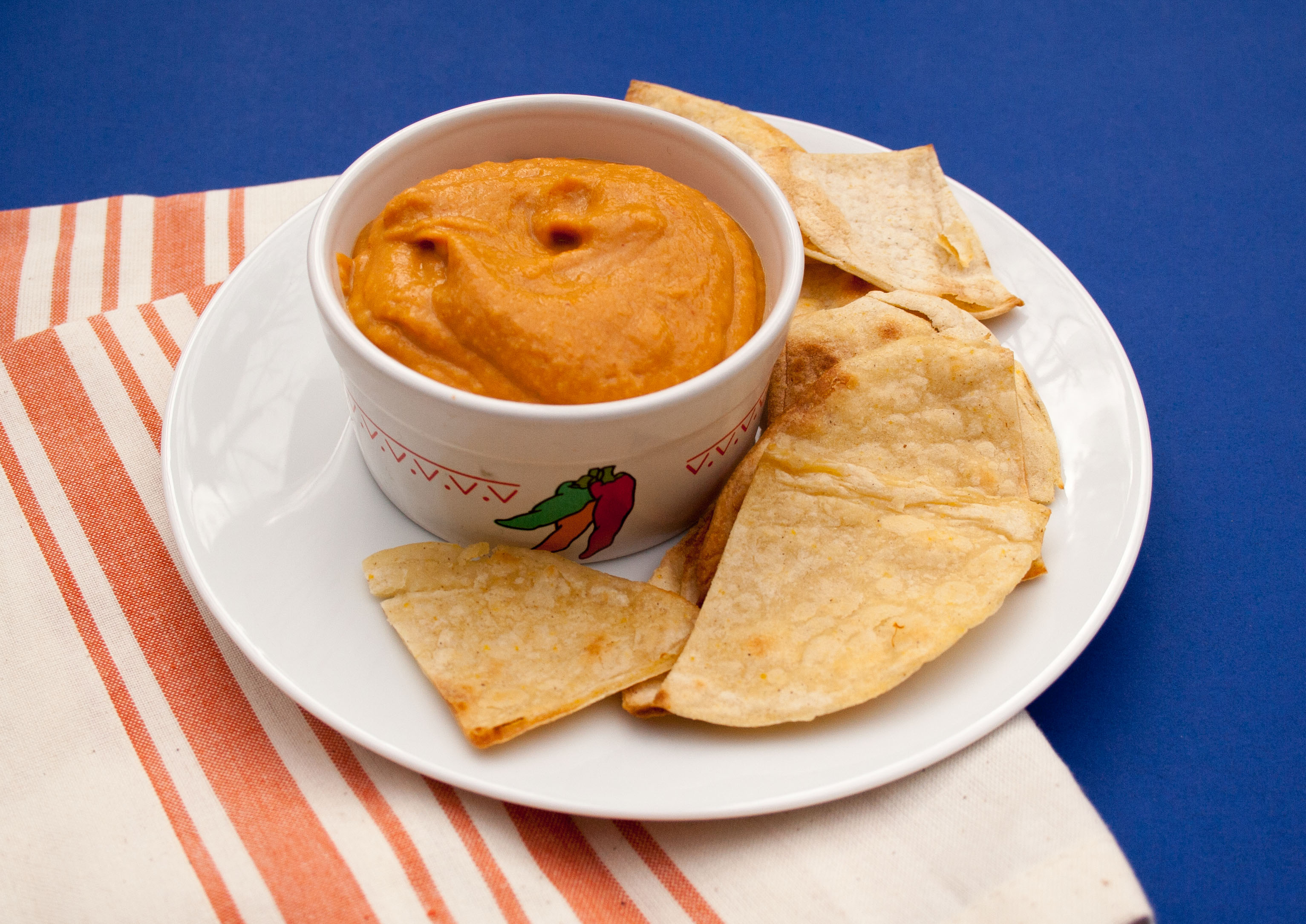 Sweet Potato Nacho Cheese with tortilla chips on a plate.