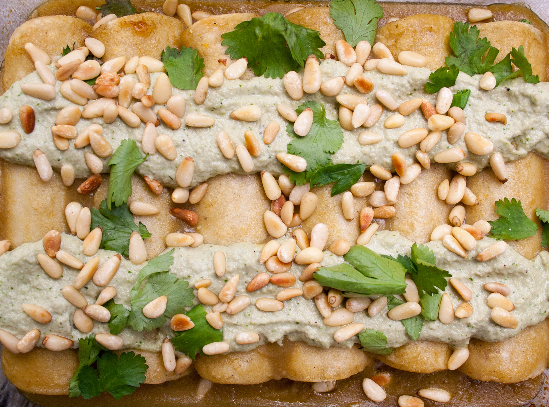 Spinach, Tofu, and Pine Nut Enchiladas birds eye view close up of enchiladas in baking dish.