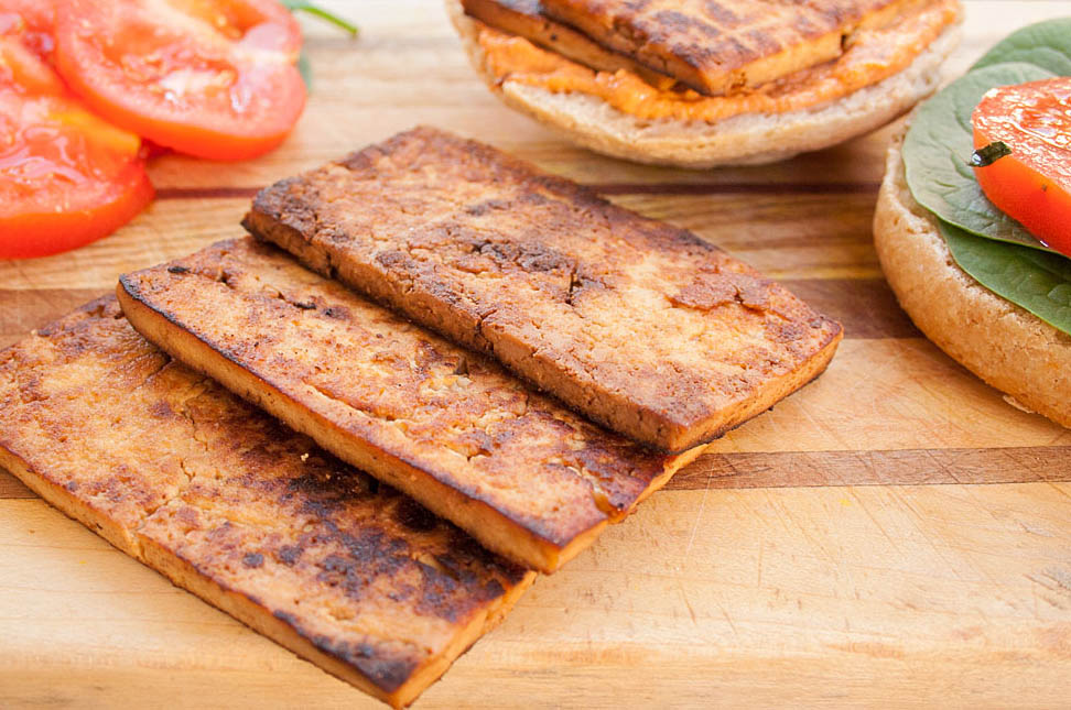 Tofu Bacon Recipe showing tofu bacon on cutting board with bread, tomatoes, and lettuce.