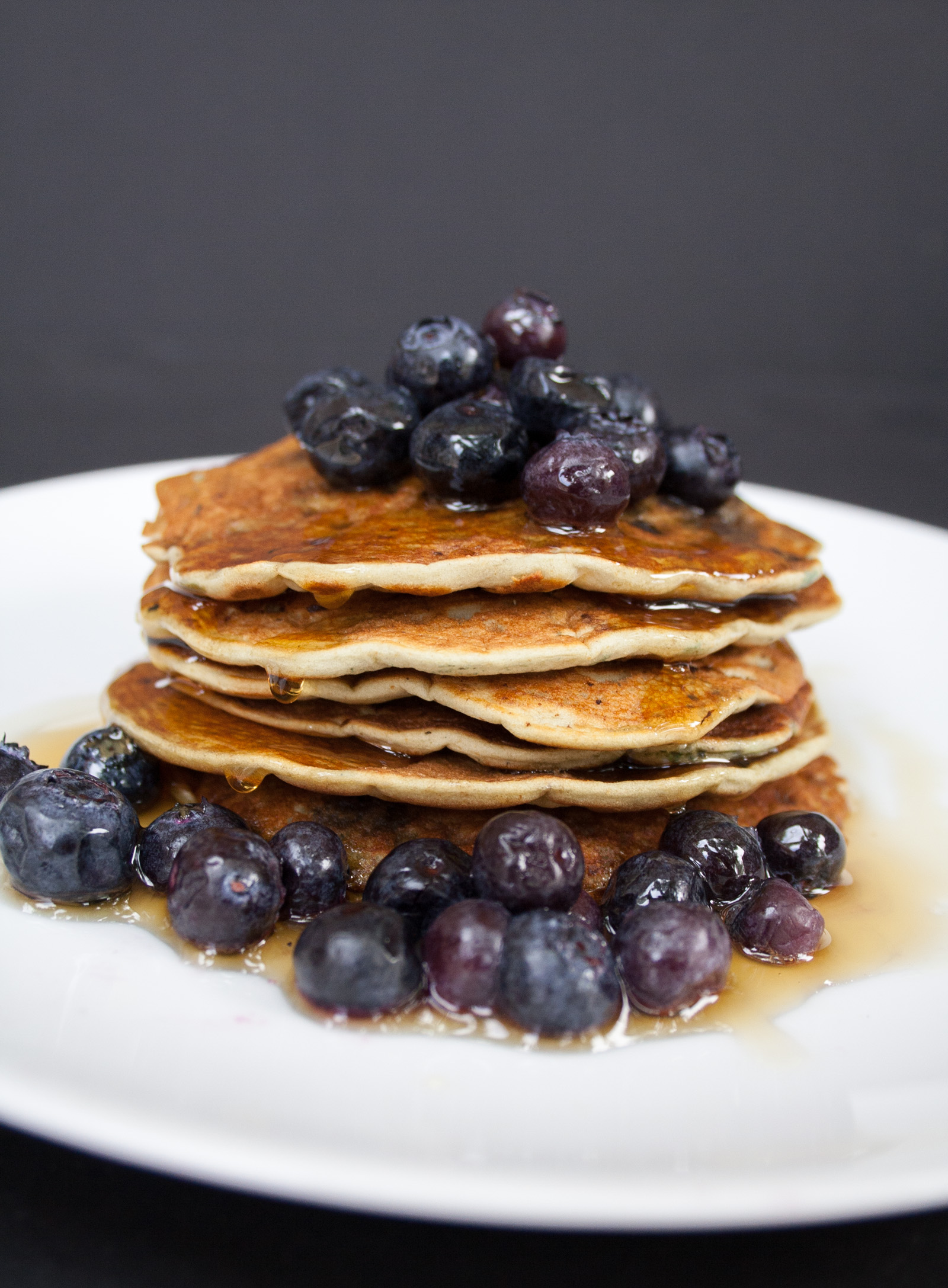 Vegan Gluten Free Blueberry Pancakes stacked with blueberries on a plate.
