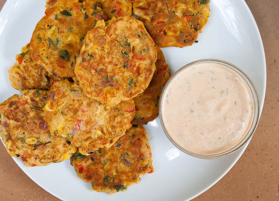 Vegan Vegetable Fritters birds eye view horizontal on a plate with vegan chipotle ranch dressing.