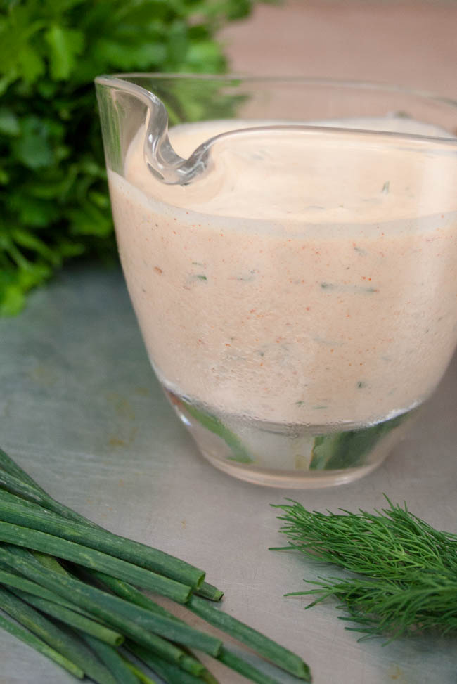 Vegan Chipotle Ranch Dressing close up with herbs in the background.