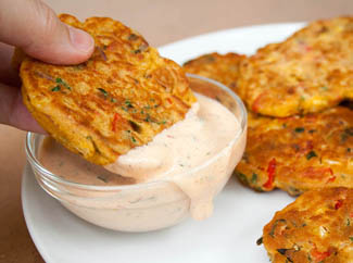 Vegetable Fritters being dunked in vegan chipotle ranch dressing.