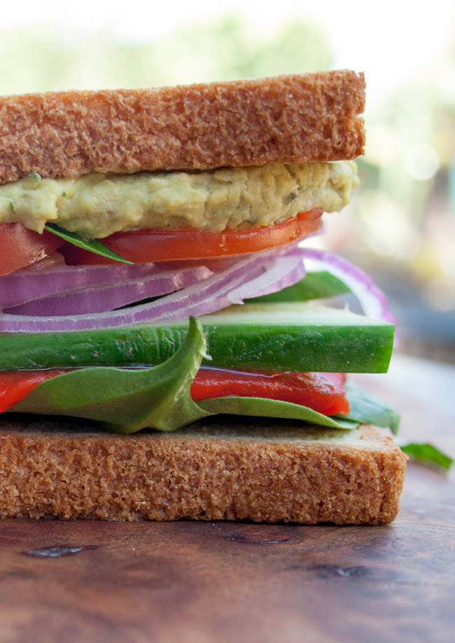 Veggie Sandwich with Basil Pesto Hummus vertical close up.