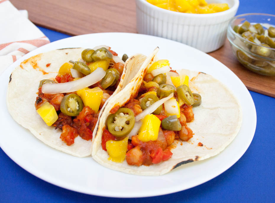 BBQ Chickpea and Mango Tacos with Pickled Peppers and Onions with chopped mango and pickled peppers and onions in the background.