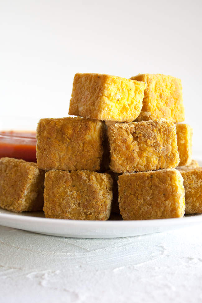 Breaded Baked Tofu Nuggets stacked on a plate.