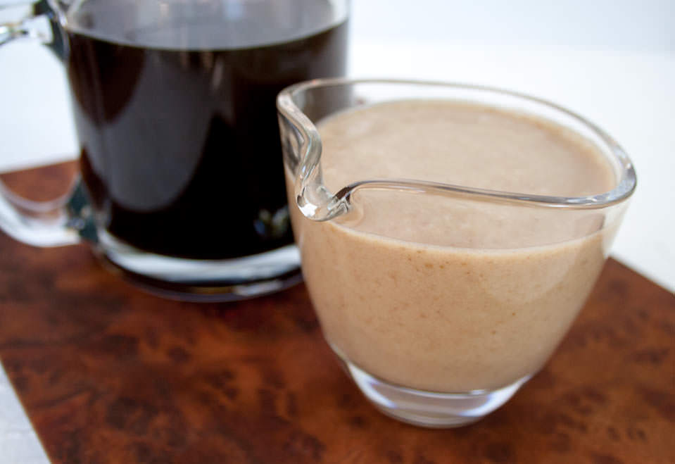 Homemade Coffee Creamer next to a mug filled with black coffee.