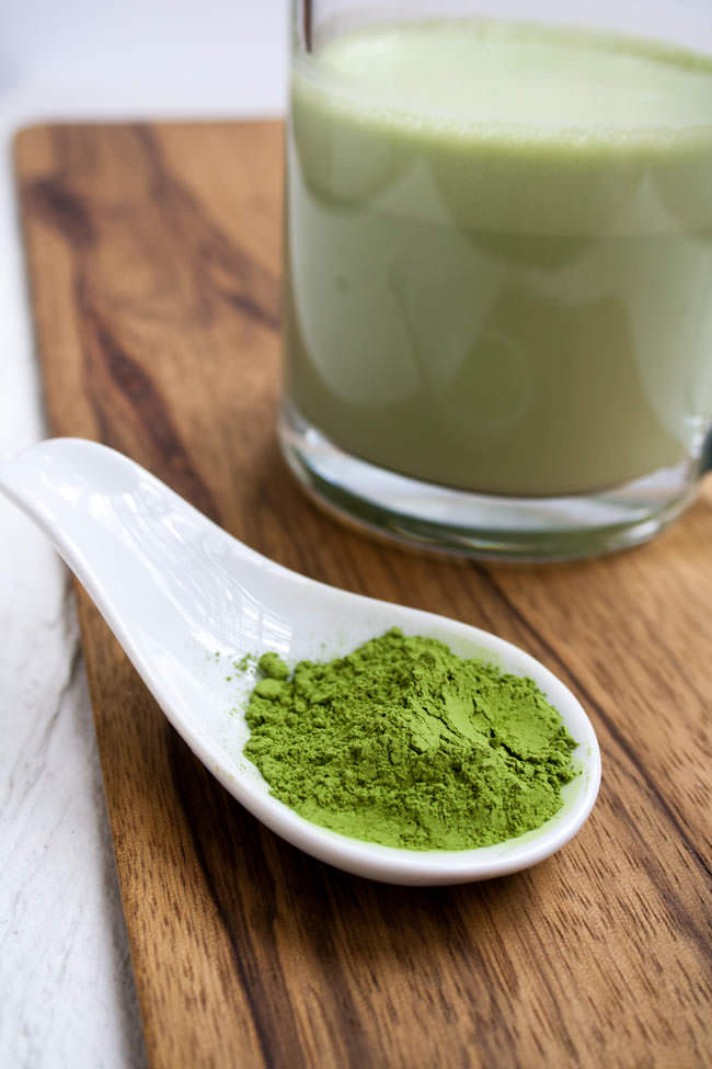 Close up of matcha green tea powder with latte in background.