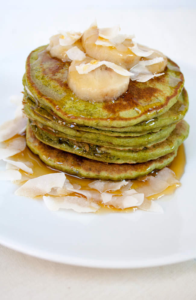 Matcha Pancakes on a plate with maple syrup, sliced banana, and coconut flakes.