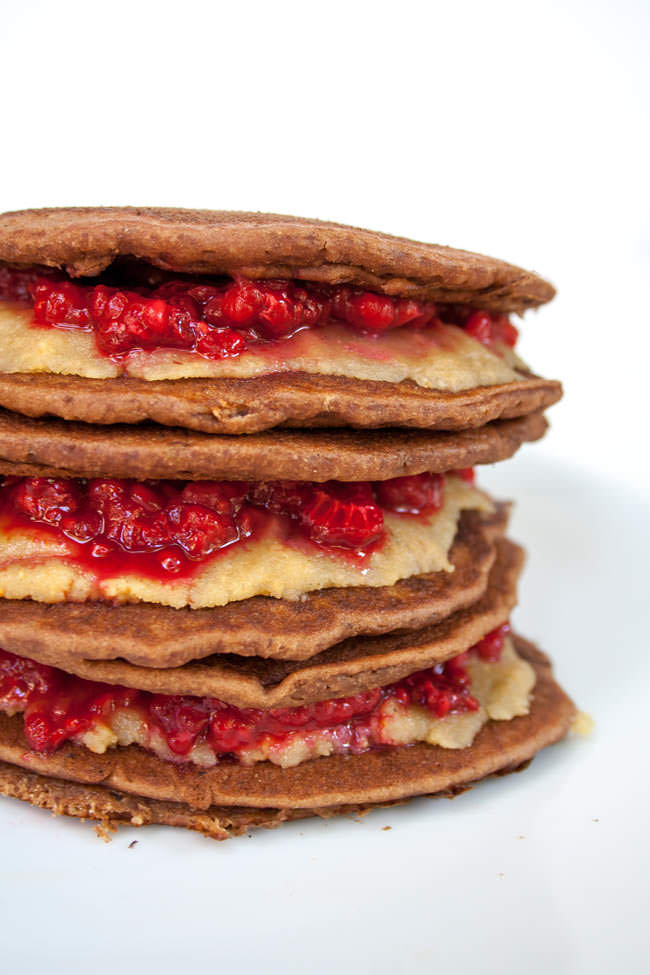 Raspberry and Almond Butter Chocolate Almond Pancake Sandwiches stacked on top of each other.