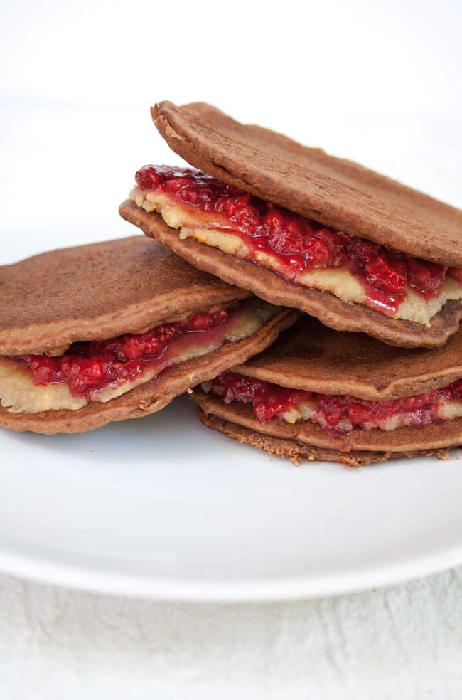 Raspberry and Almond Butter Chocolate Almond Pancake Sandwiches stacked on plate.