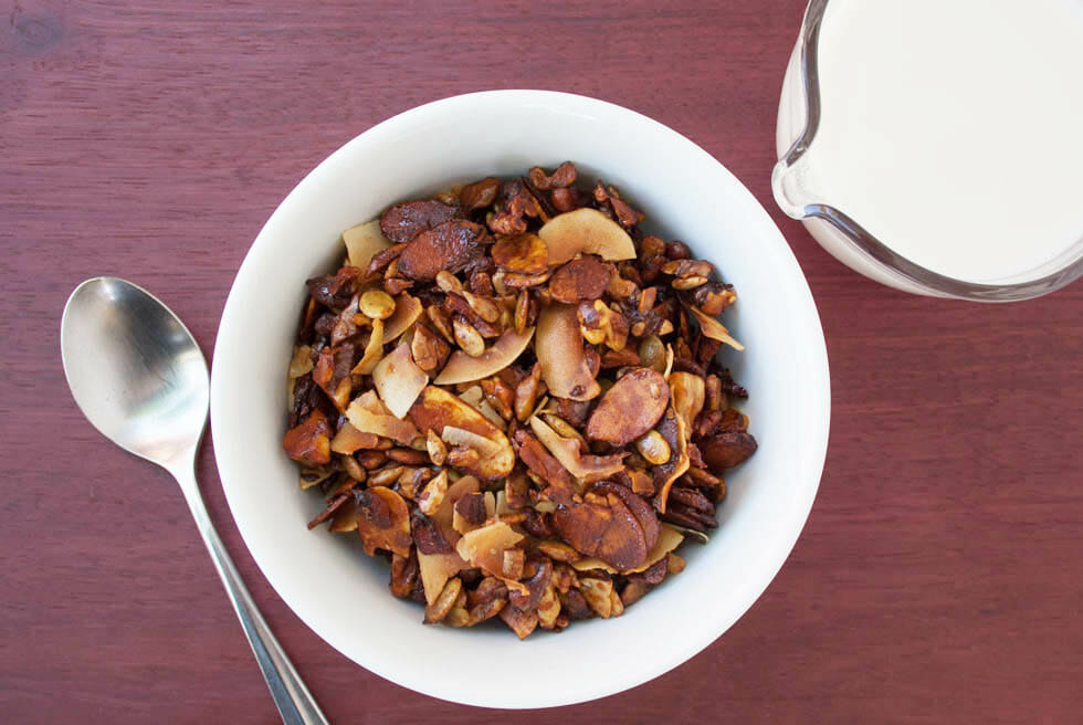 Grain Free Granola with pitcher of almond milk and spoon bird's eye view.