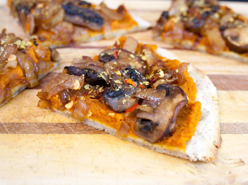 Chipotle Pumpkin Pizza with Caramelized Onions and Mushrooms close up with slices in background.