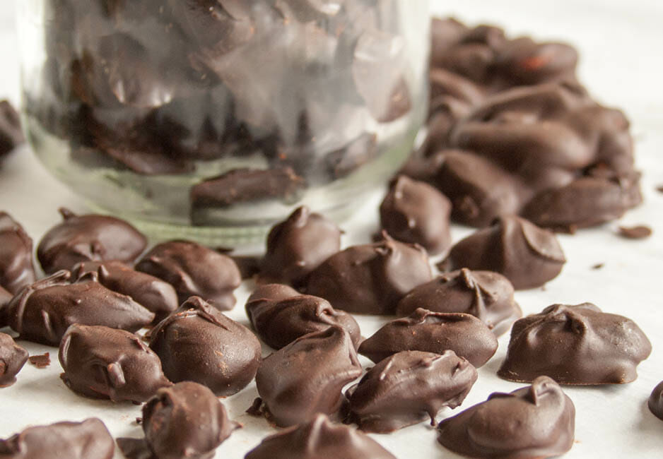 Chocolate Covered Almonds Recipe close up with jar in the background.