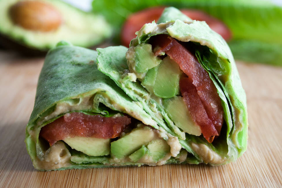 Spinach Tortilla Wrap with Avocado, Lettuce, and Tomato close up.