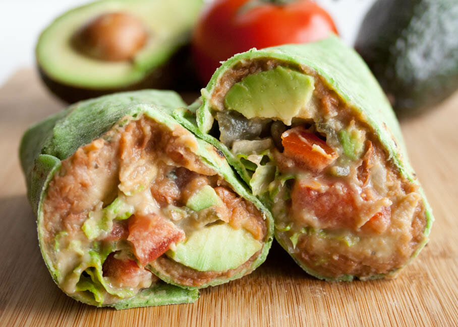 Healthy Refried Bean Burrito Recipe close up with avocados and tomatoes in the background.