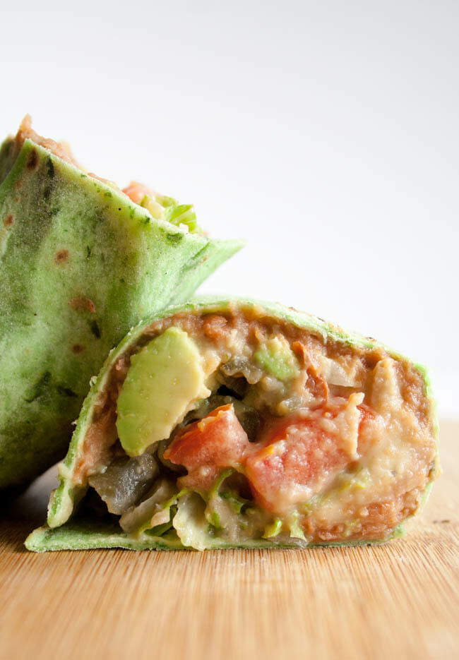 Vegan Refried Bean Burrito with Jalapeño Cilantro Hummus close up of burrito cut in half.
