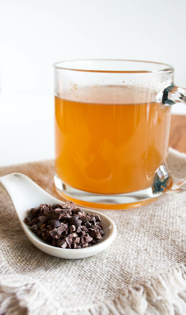 Cacao Tea in glass mug with spoonful of cacao nibs