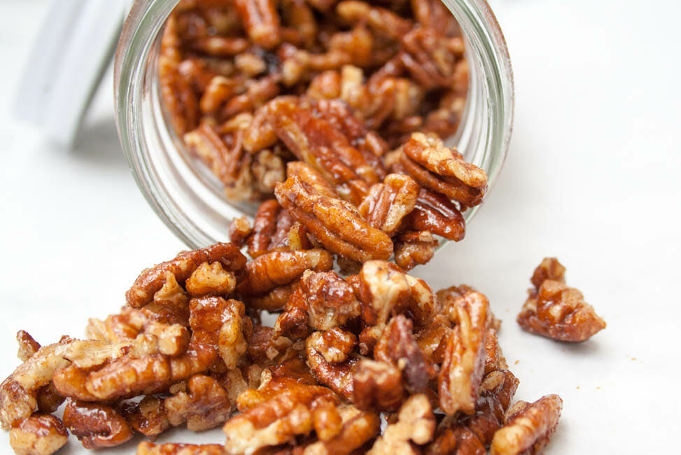 Candied Pumpkin Pie Spice Pecans spilling out of a jar.