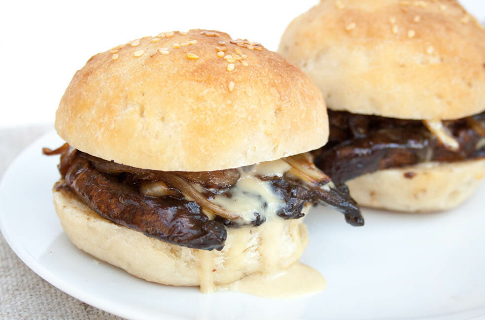 Portobello Mushroom and Caramelized Onion Sliders with maple Dijon mayo dripping out the side.