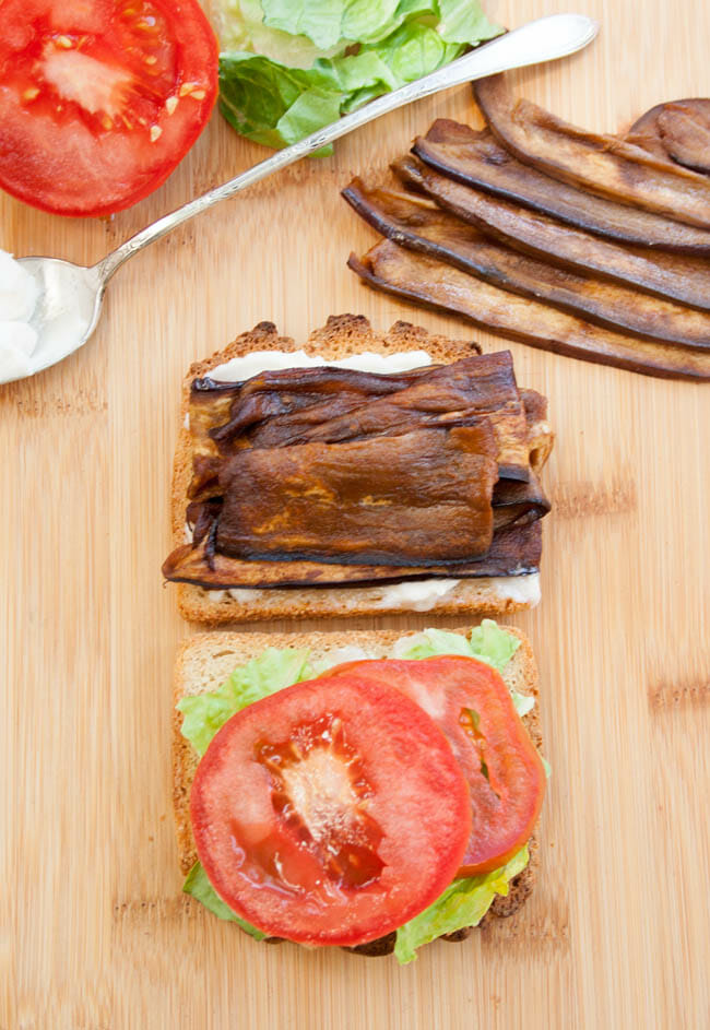 ELT (Eggplant Bacon, Lettuce, and Tomato) Sandwich open faced with ingredients in background.