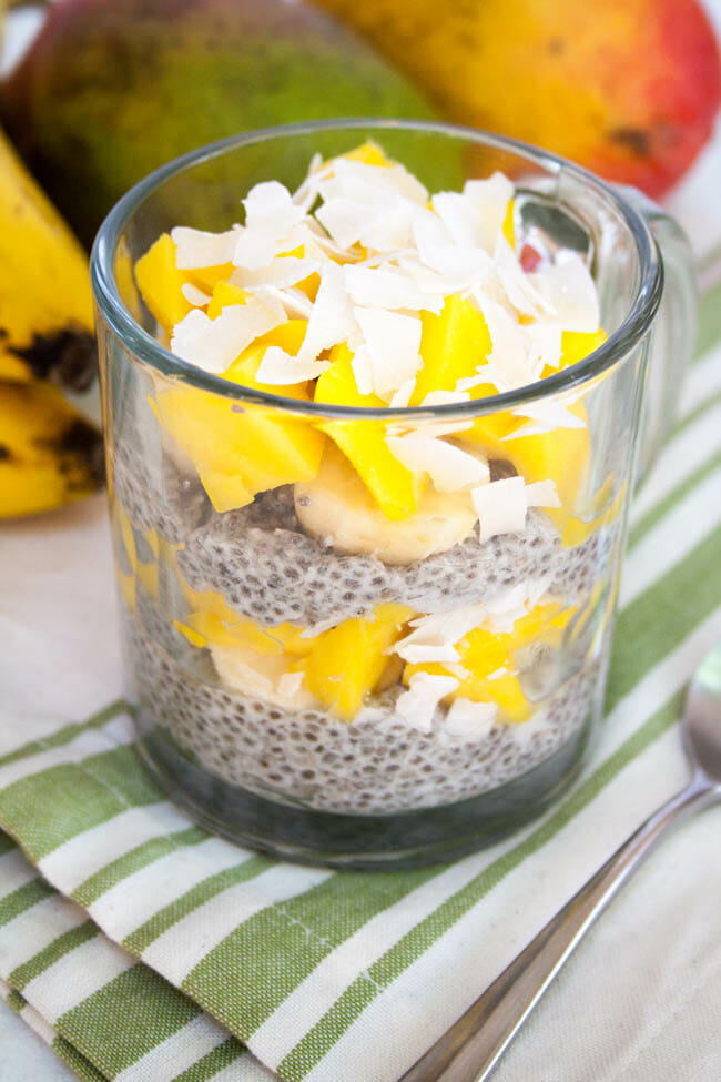 Tropical Chia Pudding with bananas and mangoes in the background.